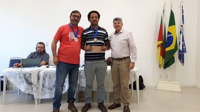 Jorge Alberto Boabaid (direita da foto) passa o comando para Valdemir Albuquerque (centro da foto) que assume a presidência do SMXC. Ritzel segue no Departamento de Xadrez da APUSM. Foto captada durante a premiação da Final do campeonato Gaúcho de 2016, realizado na sede da Associação. Foto divulgação APUSM